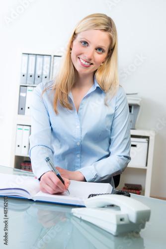 lächelnde mitarbeiterin macht sich notizen