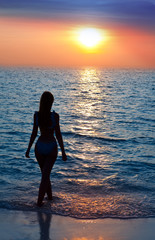 Silhouette of the sexual woman going at ocean towards to sunset