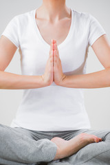 A young woman sitting in the lotus position while meditating