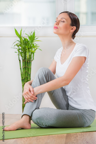 Portrait of a young beauty sitting and relaxing at home or fitne