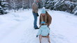 Young parents sledding his child on a park alley