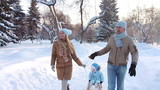 Young couple sledding his child on a sledge in winter (SLOW)