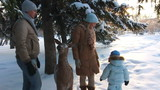 Young parents with a child standing in the winter forest