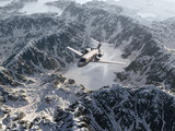 aircraft flies over a snowy mountain range