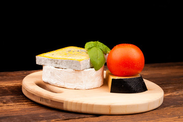 Various types of cheese and tomato isolated on black