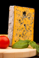 block of cheese and tomato on table and isolated on black