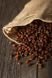 Coffee bag with coffee beans on wooden surface. Focused in cente