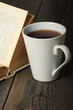 Cup of tea with old opened book on wooden surface.