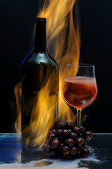 Hot wine in flame with wine glass and black grape