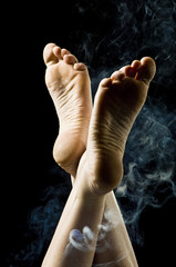 Isolated female feet surrounded by blue smoke