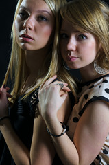 Two blonde young women in a back embrace