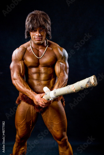 Portrait of a muscular man with a wooden club