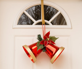 Two red christmas bells on white door