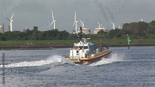 Pilot speed boat on waterway with turbines in background