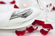 Romantic dinner setting with rose petals - 48782046