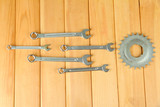 Metal cogwheel and spanners on wooden background
