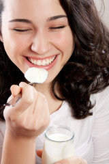 Happy woman laughing with eyes closed while eating a yogurt