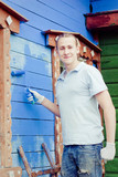 Male painter paints blue wooden wall