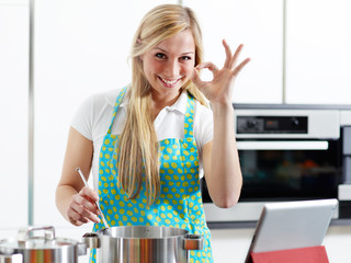 Woman in home kitchen using electronic tablet for cooking