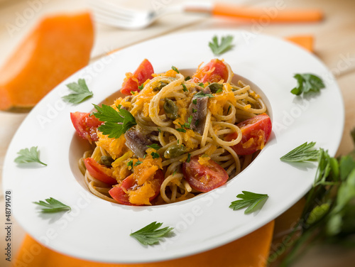 spaghetti with pumpkin anchovy caper  tomatoes, selective focus