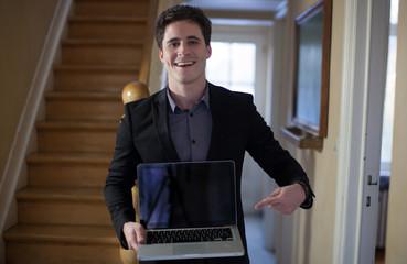 Homme montrant un ordinateur