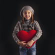 Young girl with red heart on black background.