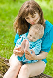 Happy mother with boy sits in grass and play with legs