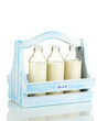 Milk in bottles in wooden box isolated on white