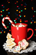 Cup of coffee with holiday candy on Christmas lights background
