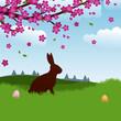 Osterhase sitzt auf Wiese unter einem Baum