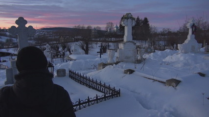 Young woman rest in cemetery during winter time