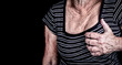 Woman suffering from chest pain isolated on black