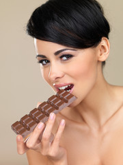 Woman biting into a bar of chocolate