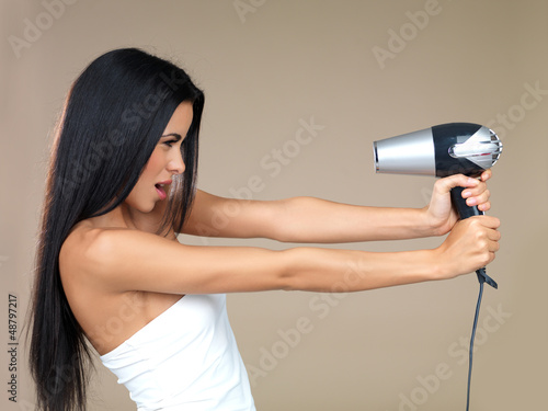 Playful woman having fun with a hairdryer