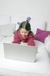 Kind liegt auf Couch und surft mit Laptop