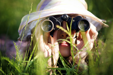 Young woman looking through binoculars in grass