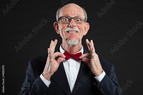 Funny senior man wearing suit and red tie.