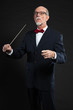 Senior conductor wearing suit. Studio shot.
