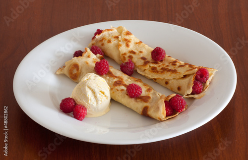 Crepes with raspberries and vanilla ice cream on a white plate