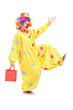 Full length portrait of a happy clown holding a bag and walking