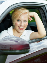 Beautiful young woman beaming with joy in her new car