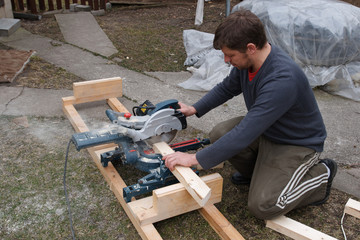 Carpenter sawing plank
