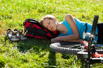 Young girl cyclist enjoying sleeps relax lying in the fresh gras