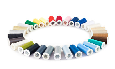 Set of colorful spools of thread on white background