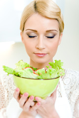 Young woman holding a bowl with vegetable salad