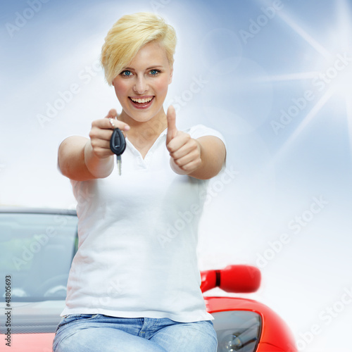 Beautiful young women shows thumb up with her electric roadster