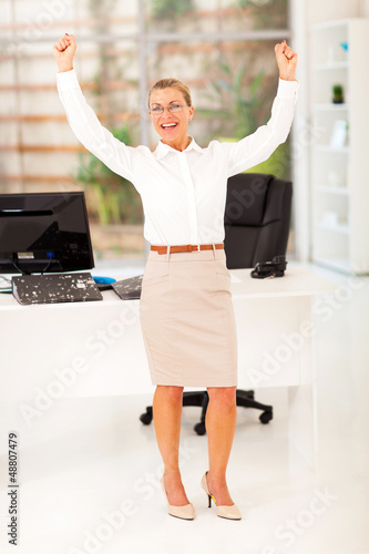 cheerful senior businesswoman waving fists in office
