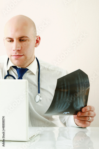 A male doctor studying a x-ray image