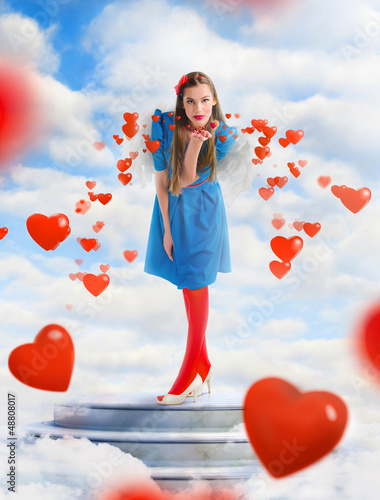 Beautiful angel woman blowing  red hearts from the sky