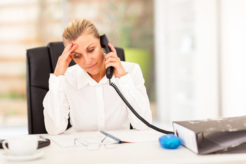 serious middle aged businesswoman talking on phone